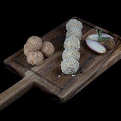 Stuffing balls in panko breadcrumbs on wooden chopping board