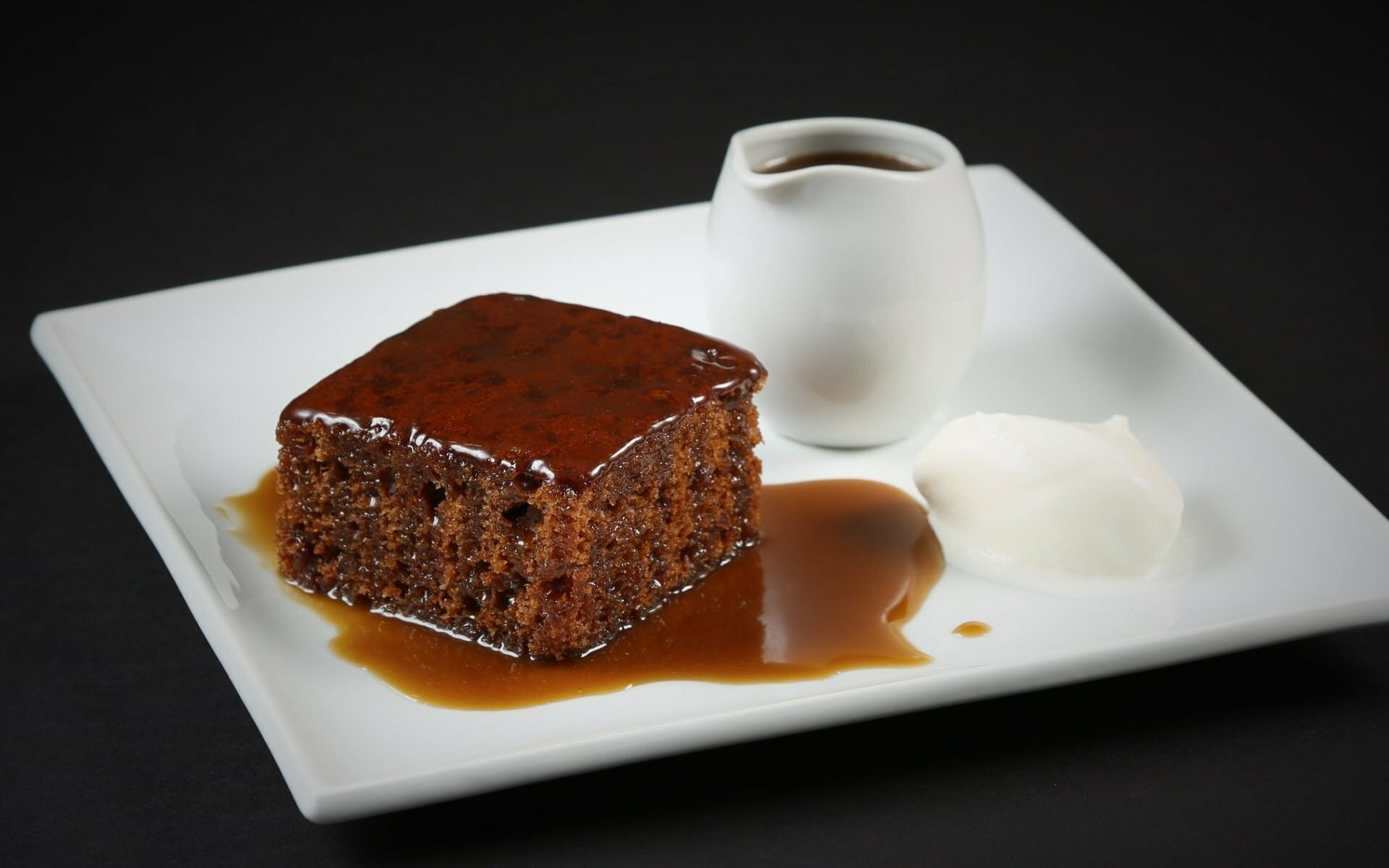 1 portion of sticky toffee pudding with ice cream on side